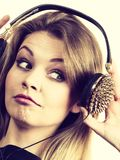 Suprised woman wearing headphones. Surprised young woman wearing grunge headphones with spikes being amazed or suprised with what she is listening Stock Photography