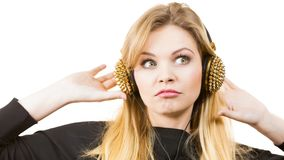 Suprised woman wearing headphones. Surprised young woman wearing grunge headphones with spikes being amazed or suprised with what she is listening Stock Images