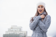 Surprised young woman with winter clothes on posing Stock Photos