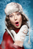 Surprised young woman in winter hat and sweater Stock Images