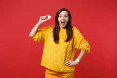 Surprised young woman in yellow fur sweater keeping mouth wide open, hold bitcoin future currency isolated on bright red. Wall background. People sincere stock photography