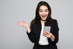 Shocking message. Surprised youngwoman holding mobile phone and staring at it while standing against grey background. Surprised youngwoman holding mobile phone Stock Image