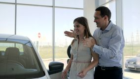 Surprises for girlfriend, Car sales center, Man Standing Behind Woman and Covering Her Eyes, Man Surprising girl with. New Car in Show Room, new auto gift stock video footage