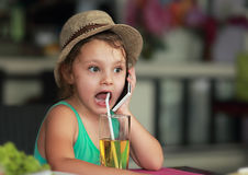 Surprising cute girl drinking juice in cafe and speaking on mobi Royalty Free Stock Images