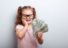 Surprising emotional kid girl holding dollars in hand and thinki Stock Photo