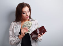 Surprising happy woman holding dollars and looking in wallet and Stock Photos