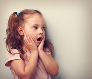 Surprising kid girl with opened mouth and hand near face looking Royalty Free Stock Images