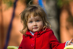 Surprising little girl dressing in red coat Royalty Free Stock Photos