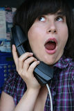 Surprising news. The girl is surprised by news heard on phone Royalty Free Stock Images