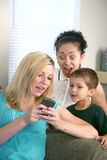 Surprising text message. A family looking at a cell phone looking ecited ot surprised Stock Photos