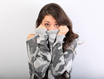 Surprising woman with big open eyes hiding her face inside the grey warm winter pullover on blue background. Closeup stock photos