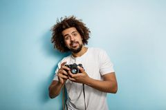 Surprisingly looking curly-headed brunet man is taking a photo. Old-fashioned camera in the hands. A joyous photographer stock photography