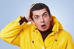 Surprsied desperated handsome man looks with bugged eyes and widely opened mouth, wears yellow anorak with hood, can`t understand Stock Photos