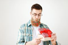 Surprsied handsome man with thick beard and mustache looks with intriguing expression as opens wrapped gift box, being Royalty Free Stock Image