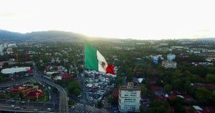 Surr-antennen sikten av en enorm mexikansk flagga som vinkar, på solen, döljer tillbaka bak bergen Många bilar genomreser för ave lager videofilmer