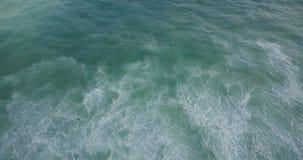 Surr som tillbaka flyger bak en havvåg över fantastisk naturlig seafoamtextur av blått och mintkaramellgräsplan som stiger upp arkivfilmer