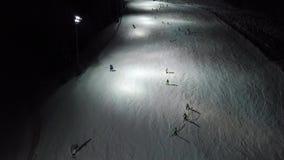 Surra den flyg- sikten av skidåkare på lutningen, nattskidåkning på Monte Pora skidar semesterorten stock video