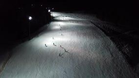 Surra den flyg- sikten av skidåkare på lutningen, nattskidåkning på Monte Pora skidar semesterorten lager videofilmer