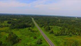 Surra flyget över huvudvägen bland de gröna skogarna arkivfilmer