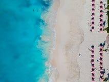 Surra fotoet av stranden med röda paraplyer i Grace Bay, Providenci fotografering för bildbyråer