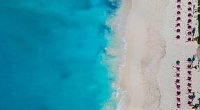 Surra panorama av stranden med röda paraplyer i Grace Bay, ge royaltyfri fotografi