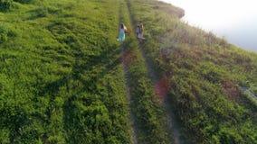 Surra sikten, det aktiva barnet med flickvänner med kulöra band i armar spenderar fritid på grön gräsmatta stock video