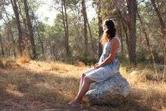 Surreal blurred background of young woman sitting on the tsone in forest Stock Photos