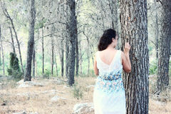 Surreal blurred background of young woman stands in forest. image is retro toned Royalty Free Stock Image