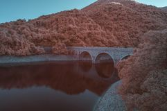 Surreal bridge in infrared colors. Took with IR 650nm,bridge next to small mountains, lake below, surrounded by lots of trees, dreamy colors Royalty Free Stock Photography