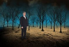 Surreal Business, Sales, Marketing, Goals. Abstract concept for sales, business, and marketing. A businessman stands in a desolate desert with dead trees royalty free stock images