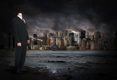 Surreal Businessman, Business Man, Apocalypse. A surreal businessman stands with a city skyline where the urban area is being destroyed in an apocalypse. The stock photos
