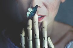 Surreal butterfly leaning of a wooden hand touching a woman`s mouth