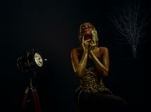 Surreal creative portrait of sexy african american model with glossy gold wig and makeup posing to the camera in black Royalty Free Stock Images