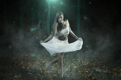 Surreal dancer in fairy forest Stock Photos