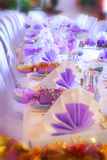 Surreal dining setting. Wedding or birthday table setting of napkins, glasses, cutlery and crackers (bonbons) with additional blur, exposure and saturation work Royalty Free Stock Images