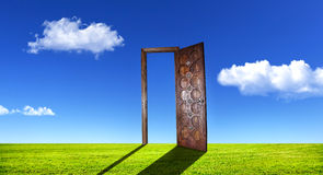 Surreal door on grass. Opened wooden door on green grass at blue sky with white clouds Royalty Free Stock Photos