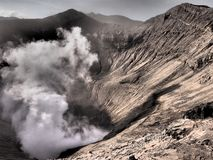 Java, Indonesia: Dramatic light at Mt Bromo's caldron. Volcanic smoke drifts up the cone just after sunrise at Mount Bromo, Java, Indonesia.This volcano is in Royalty Free Stock Image