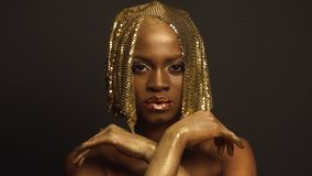 Surreal Fashion Portrait of African American Female Model with Golden Glossy Headwear. Creativity concept, black studio stock video