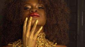 Surreal Fashion Portrait of African American Female Model with Golden Glossy Headwear. Creativity concept, black studio stock footage
