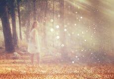 Surreal foto die van jonge vrouw zich in bosbeeld bevinden is geweven en gestemd Dromerig concept Royalty-vrije Stock Afbeeldingen