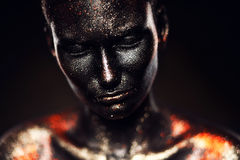 Surreal girl in black paint with glitter Stock Image