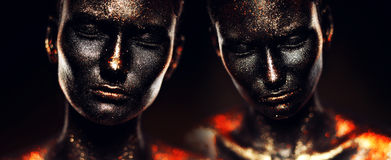 Surreal girls in black paint with glitter. In studio Stock Photography