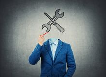Surreal image as a businessman with invisible face holding a pencil in his hand draw wrench and screwdriver tools iconl instead of royalty free stock images