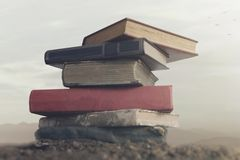 Surreal image of giant books on top of each other touching the sky royalty free stock photo