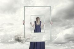 Surreal image of a woman holding a frame that reflects herself. A surreal image of a woman holding a frame that reflects herself royalty free stock photo