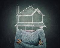 Surreal image young woman architect with crossed armss and house sketch instead of head drawn over blackboard background. Home of stock illustration