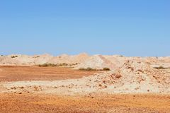 Surreal landscape around mining town Coober Pedy, South Australia. Surreal desert landscape with pink hills and a blue sky, an industrial area around opal mining Stock Images