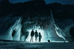Surreal landscape with people exploring mysterious ice grotto cave. Outdoor adventure. Family exploring huge icy cave. Dark majestic landscape. Magical stock photos