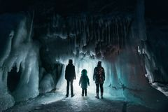 Surreal landscape with people exploring mysterious ice grotto cave. Outdoor adventure. Family exploring huge icy cave. Dark majestic landscape. Magical royalty free stock photos