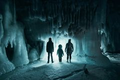 Surreal landscape with people exploring mysterious ice grotto cave. Outdoor adventure. Family exploring huge icy cave. Dark majestic landscape. Magical royalty free stock photography